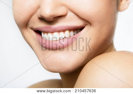 Laughing woman mouth with great teeth over white background. Healthy beautiful female smile. Teeth health, whitening, prosthetics and care. stock photo