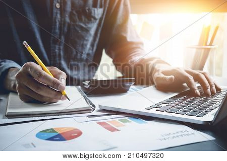A Man Analysis Business Document With Laptop Computer Counting With Cost And Writing Make Note At Of