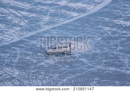Wide view of Isolated grey van car and a man on frozen lake Khovsgol in winter at Mongolia, Beautiful landscape of ice texture crack and line surface, The lone man in brown coat open back door of car on center of ice blue ground near hole stock photo
