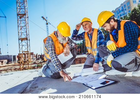 Construction Workers With Building Plans