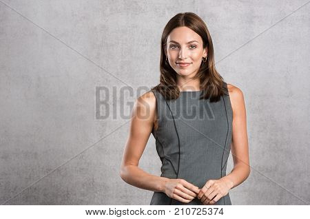 Young business woman feeling confident standing against grey wall with copy space. Portrait of beaut