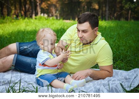 handsome man resting with his son in forest, young guy playing with little son in park stock photo