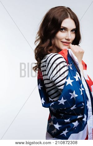 Love my nation. Pretty auburn-haired young woman posing for the camera while standing half-turned and wrapped into an American flag stock photo