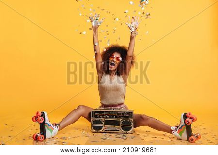 Emotional african disco woman in retro wear and roller scates throwing confetti while sitting with boombox, isolated on yellow background stock photo