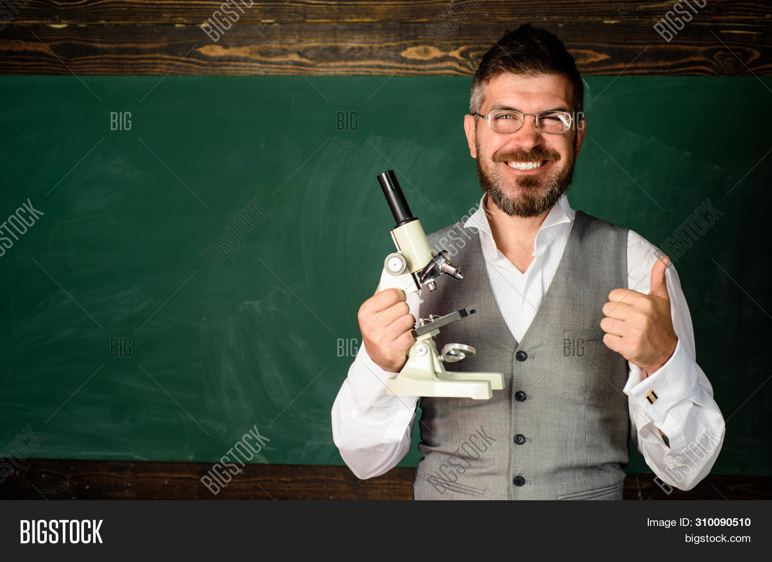 Teacher In Classroom At Elementary School. Teacher Giving Lesson To Students. Confident Male Teacher