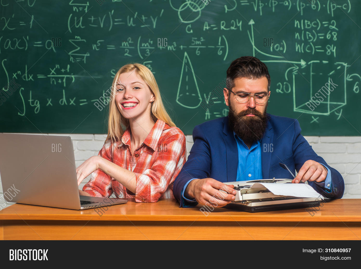 Young Teacher Near Chalkboard In School Classroom. Teacher Collaborates With Colleagues. Teacher And