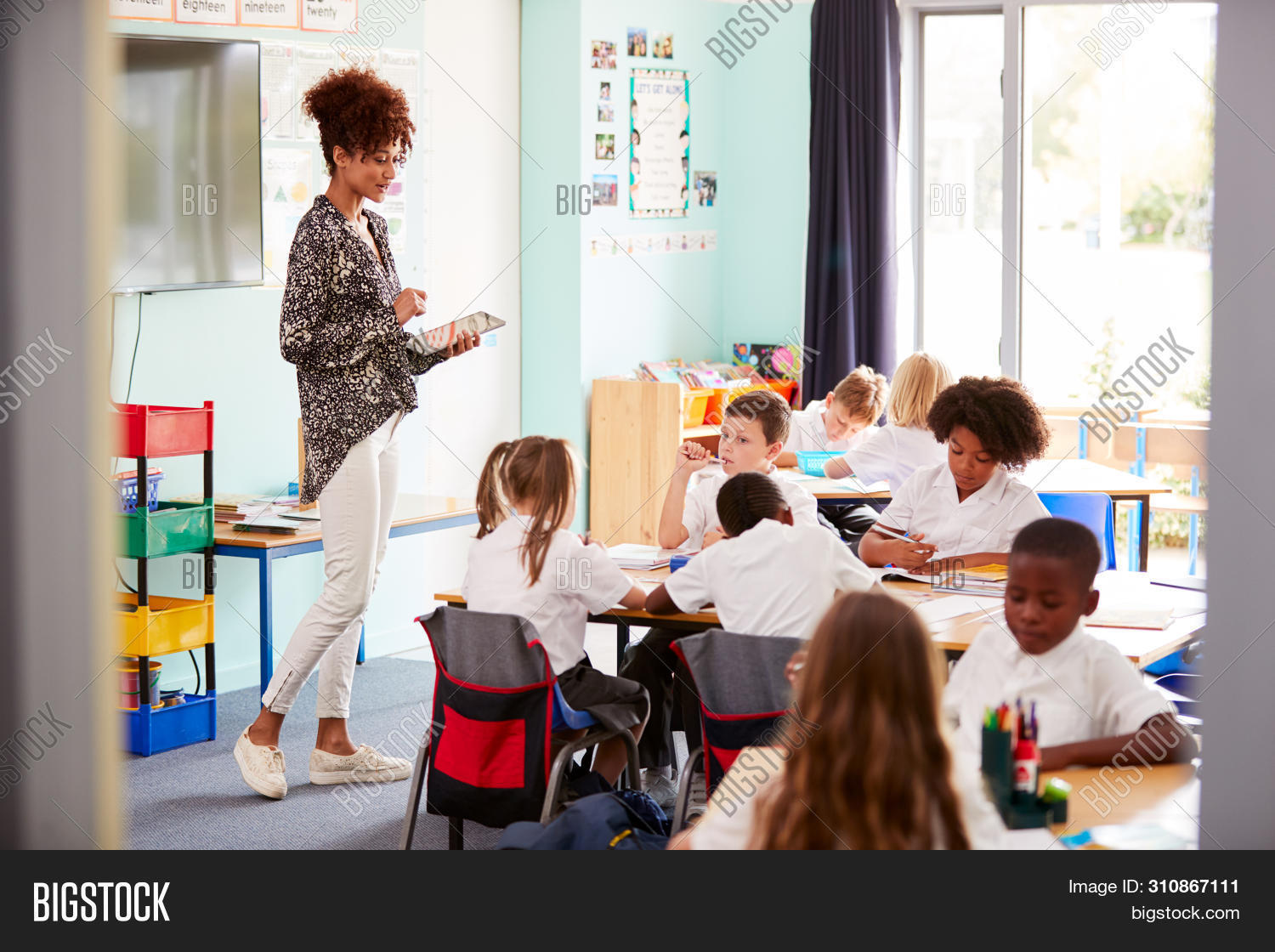 20s,7 years old,8 years old,african american,black,boy,caucasian,child,children,class,classroom,connected,desk,digital tablet,education,elementary,female,front view,girl,group,horizontal,independent school,learning,listening,male,multi-cultural,occupation,online,people,person,primary,private school,public school,pupils,school,sitting,smiling,students,tablet computer,teacher,teaching,technology,together,touchscreen,twenties,uniform,woman,women