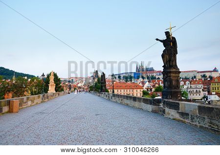 Amazing view of famous Charles Bridge in Prague, Bohemia, Czech Republic photographed in the early morning in sunrise light with almost no tourists. Prague Castle in background. Tourist places stock photo