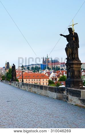 Vertical picture of Charles Bridge in Prague, Bohemia, Czech Republic taken in the early morning in sunrise light with almost no people. Prague Castle in background. Tourist attraction stock photo