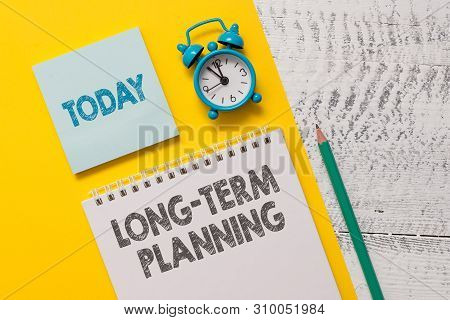 Text sign showing Long Term Planning. Conceptual photo Establish Expected Goals five or more years ahead Spiral notepad paper sheet marker alarm clock retro wooden background. stock photo