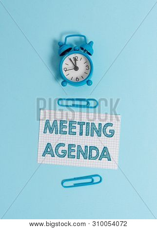 Handwriting text writing Meeting Agenda. Concept meaning items that participants hope to accomplish at a meeting Alarm clock wakeup squared blank paper sheet clips colored background. stock photo