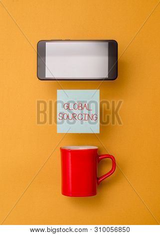 Word writing text Global Sourcing. Business concept for practice of sourcing from the global market for goods Coffee cup colored sticky note electronic device yolk color background. stock photo