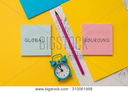 Text sign showing Global Sourcing. Conceptual photo practice of sourcing from the global market for goods Notepads marker pen colored paper sheets alarm clock wooden background. stock photo