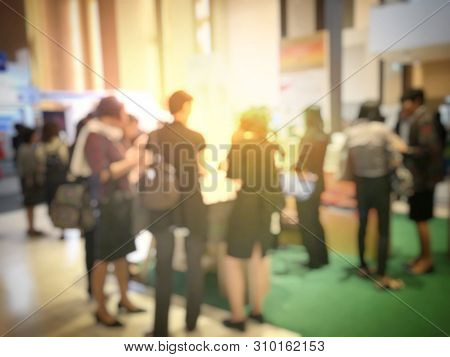 blurred image of people walking on a trade fair exhibition or expo where business people show innovation activity and present product in a big hall. stock photo
