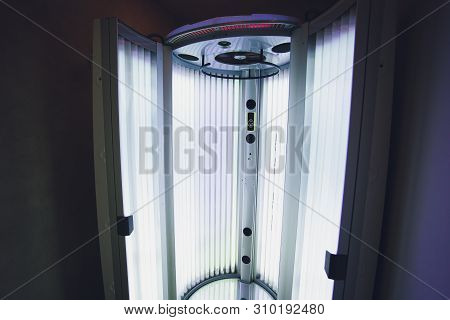 Vertical Tanning turbo Solarium Light Machine with glowing blue light ultraviolet lamps for tanning and skin care. Empty tanning Modern solarium, inside. Open Solarium door. Control panel on the side. stock photo