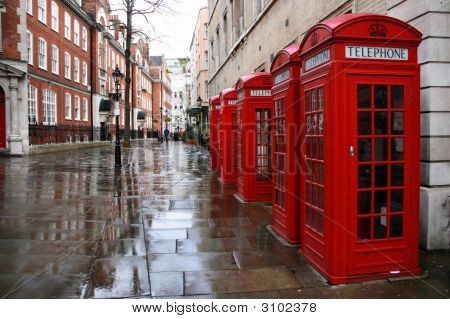 Row of phone booths in rainy London. Street view. stock photo