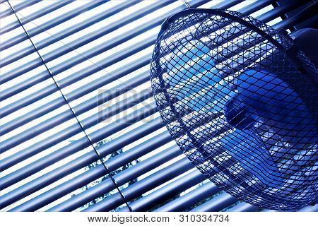 Blinds and fan is an effective protective device against the summer heat. The slats of the blinds to turn and regulate the light and air flow. Blinds and fans are popular in residential, office and industrial areas. stock photo