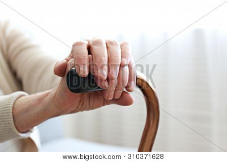 Elderly woman sitting in nursing home room holding walking quad cane with wrinked hand. Old age senior lady wearing beige cardigan, metal aid stick handle bar close up. Interior background, copy space stock photo