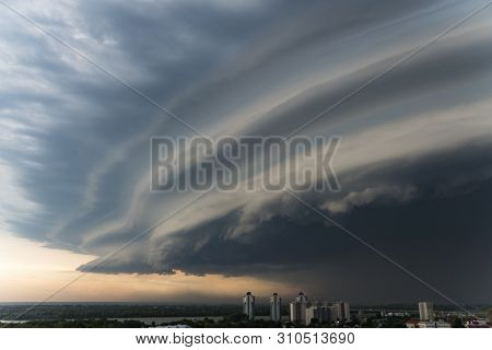 A storm cloud is approaching the city. Bad weather. A dark cloud eclipses the sky. severe storm. Lenticular clouds stock photo