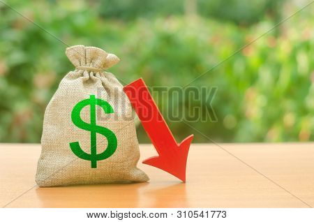 Money bag with dollar symbol and red arrow down. Reduced profits and liquidity of investments. Reduced tax revenues, economic difficulties, departure of capital, investors. Falling wages and welfare stock photo