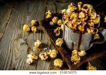 Homemade sweet caramel pop corn, with caramel topping, dark rustic background copy space stock photo