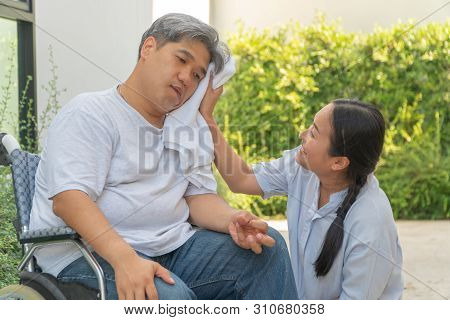 Middle-aged and obese men are paralyzed, Crooked mouth, Crinkled hands and Limb weakness  In the wheelchair and there is a wife using a towel on the face of her husband with love and good hope stock photo