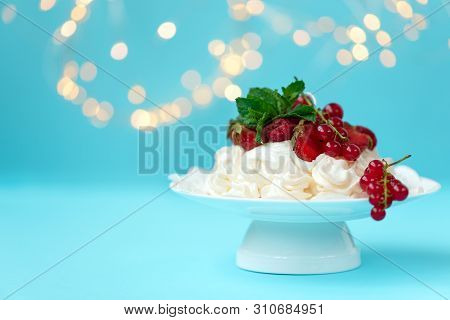 Pavlova birthday fruit cake with strawberry, raspberry, red currant and mint leaves on pastel blue background against blurred lights. Selective focus. Healthy food or birthday celebration concept. Copy space stock photo