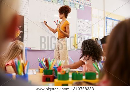 Female Teacher Standing At Whiteboard Teaching Maths Lesson To Elementary Pupils In School Classroom stock photo