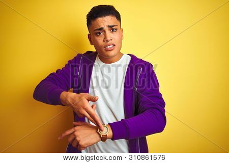 Young brazilian man wearing purple sweatshirt standing over isolated yellow background In hurry pointing to watch time, impatience, upset and angry for deadline delay stock photo