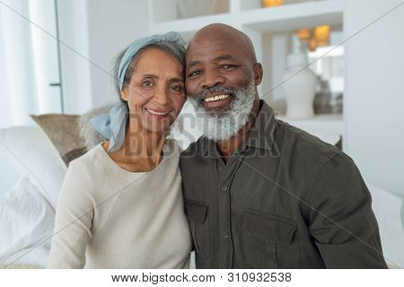 Front view of diverse senior couple smiling while sitting on a couch inside a room in beach house. Authentic Senior Retired Life Concept stock photo