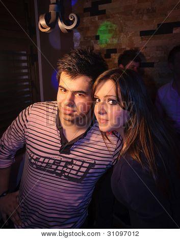 Young teen couple posing in night bar. stock photo