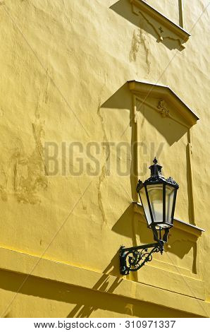Detail of yellow facade of historical building in the old town of beautiful Prague, Czech Republic. Golden hour photography. Sun shining on the facade. Street lamp. Art. Praga, Czechia, Europe stock photo