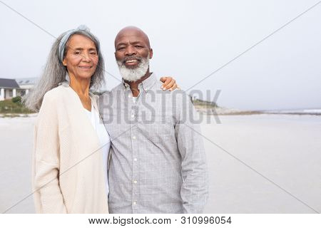 Front view of happy senior African-American couple standing on the beach on cloudy day. Authentic Senior Retired Life Concept stock photo