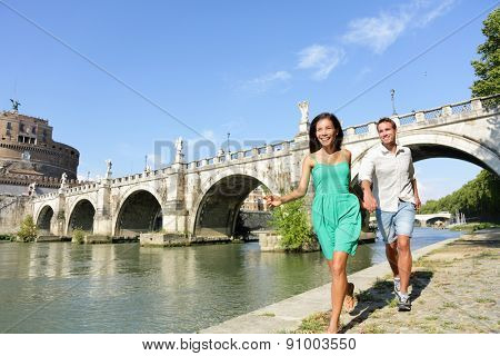 Romantic couple tourists walking Castel Sant Angelo, Rome. Happy romantic couple looking at the roman castle enjoying their romantic summer holiday travel in Italy, Europe. Man and woman holding hands stock photo