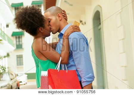 Black tourist heterosexual couple in Casco Antiguo - Panama City with shopping bags. The girl hold a credit card and kisses her boyfriend stock photo