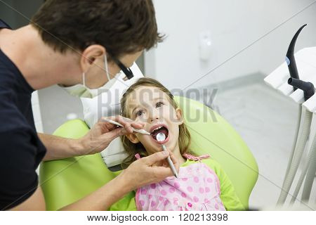 Child patient sitting on dental chair in paediatric dentists office on her regular checkup for caries and gum disease. Early prevention oral hygiene and milk teeth care concept. stock photo