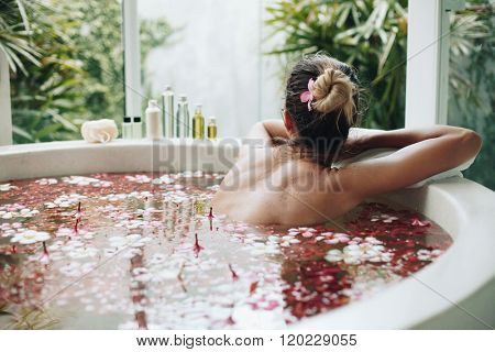 Woman relaxing in round outdoor bath with tropical flowers, organic skin care, luxury spa hotel, lif