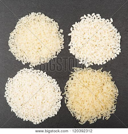 Rice background uncooked raw cereals macro closeup. Various color and shape varieties of rice on black slate tray stock photo