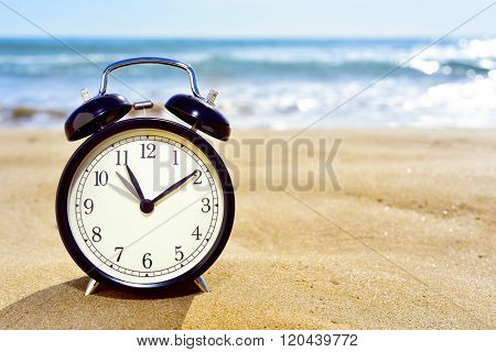 closeup of an alarm clock on the sand of a beach adjusting forward one hour at the beginning of the