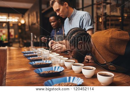 Modern roastery with three baristas training with a variety of roasted coffee beans and freshly made ground coffee at a wooden counter stock photo
