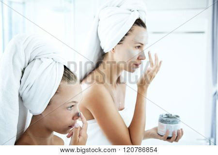 Mother and tween daughter make a clay facial mask, family skin care in the bathroom stock photo