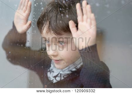 Young 7 years old boy standing beside the window with raindrop on the glass after rain. Rainy Day stock photo