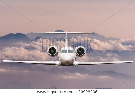 Travel concept. Front view of Jet airliner in flight with sky, cloud and mountain background. Commer