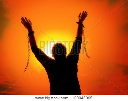 Silhouette of man agains the sunset ssky raising up his hands as he becomes free from chains and sha