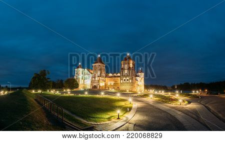 Mir, Belarus. Mir Castle Complex In Evening Illumination Lighting. Famous Landmark, Ancient Gothic Monument Of Feudalism Under Blue Night Sky. UNESCO Heritage. Panorama, Panoramic View Shot stock photo
