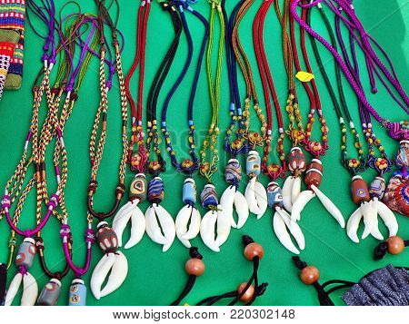 Aboriginal handmade jewelry and necklaces with colorful glass beads and animal teeth for sale at a market stock photo