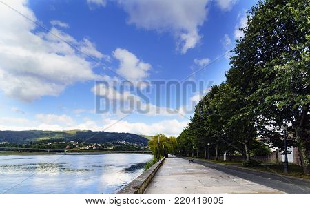 Wide angle photo of the promenade in the bay of Pontedeume in La Coruna, Spain with mountains with houses and a blue sky with white clouds stock photo