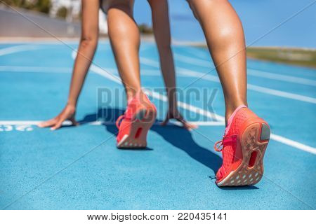Sprinter waiting for start of race on running tracks at outdoor stadium. Sport and fitness runner wo