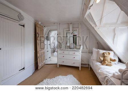 Beautifully decorated bedroom within 16th Century English cottage decorated in shades of white featuring sloping floors and misaligned doorways, chest of drawers, childs daybed with teddy bear mirror and adjoining room stock photo