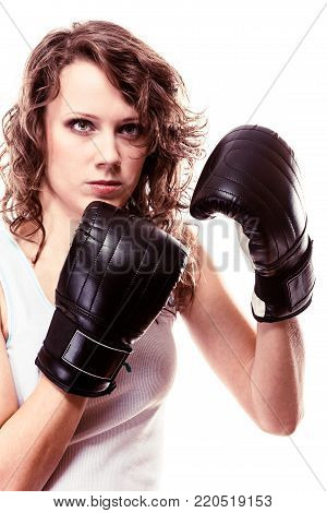 Martial arts or emancipation idea concept. Sport boxer woman in black gloves. Fitness girl training kick boxing showing her power domination. Isolated on white background. stock photo